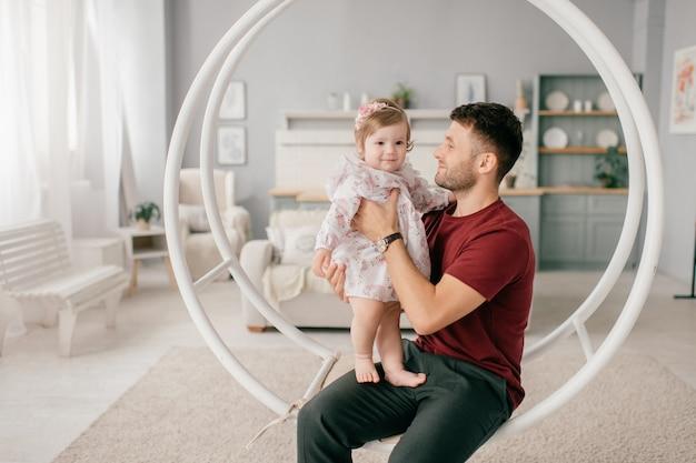 かわいい小さな娘と明るい部屋でハンサムな強い男が丸いブランコに座っています。
