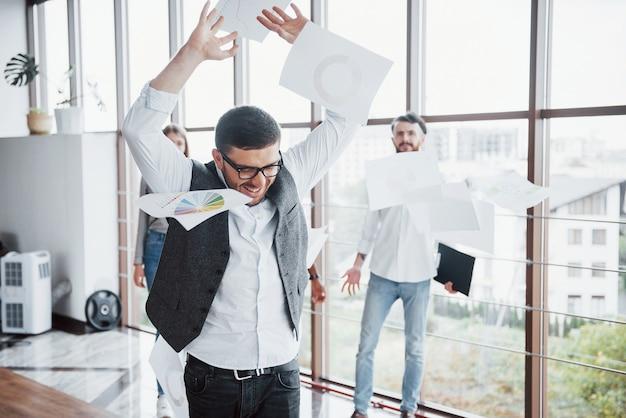 사무실에서 잘 생긴 젊은 노동자 팀이 사건에 서명하는 기쁨에 대한 문서를 던지고 있습니다.