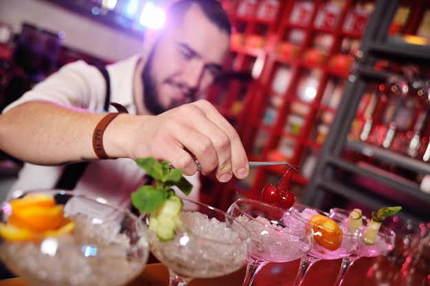 Красивый молодой бармен готовит коктейли и кладет вишни для коктейлей на поверхность бара или ночного клуба.