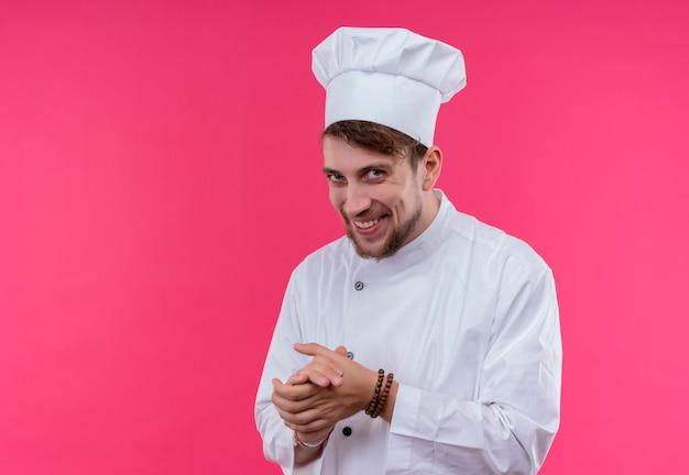 Красивый молодой бородатый шеф-повар в белой форме улыбается и держится за руки, глядя на розовую стену