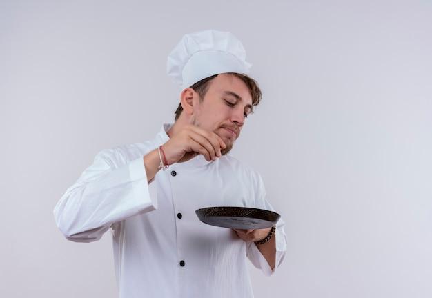 白い炊飯器の制服と白い壁にフライパンを保持している帽子を身に着けているハンサムな若いひげを生やしたシェフの男
