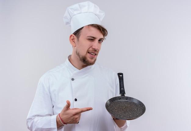 Красивый молодой бородатый шеф-повар в белой униформе и шляпе, указывая на сковороду, глядя на белую стену