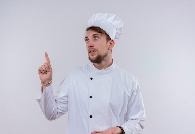 Красивый молодой бородатый шеф-повар в белой униформе и шляпе, указывающий вверх указательным пальцем на белой стене