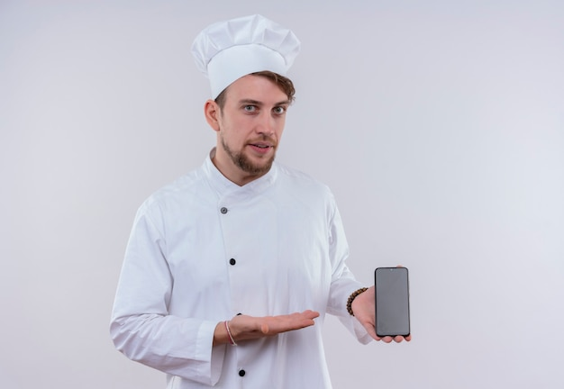 흰 벽에 휴대 전화의 빈 공간을 보여주는 흰색 밥솥 유니폼과 모자를 쓰고 잘 생긴 젊은 수염 난 요리사 남자