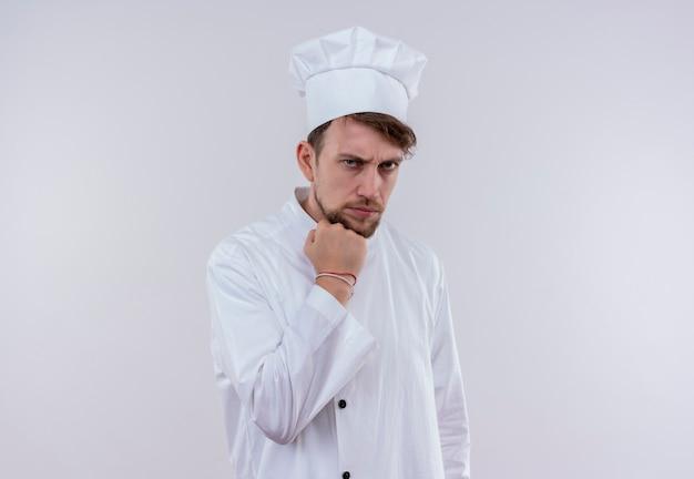 Красивый молодой бородатый шеф-повар в белой униформе и шляпе показывает сжатый кулак и агрессивно смотрит на белую стену