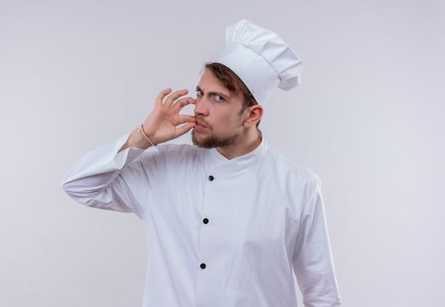 Красивый молодой бородатый шеф-повар в белой униформе и шляпе показывает вкусный знак ок пальцами, серьезно глядя на белую стену