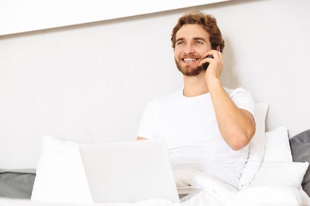 집에서 침대에서 잘 생긴 젊은 수염 난된 남자가 휴대 전화로 이야기.