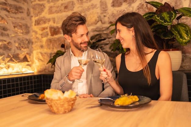 レストランで恋をしているハンサムな若いカップル、ワインのグラスを乾杯、バレンタインを祝う