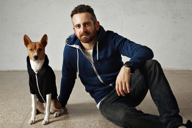 Красивый молодой человек и коричнево-белая собака в одинаковых темных толстовках на белом