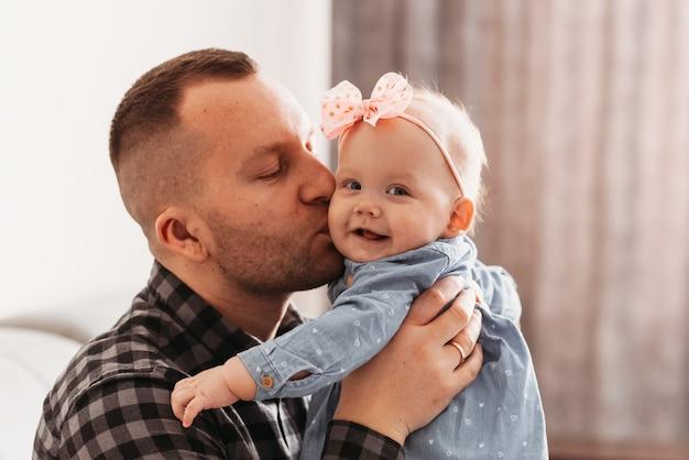 ハンサムな若い男の父は小さな娘にキスします。パパの腕の中で幼児