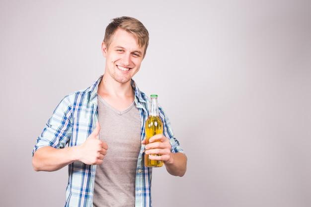 親指を立ててビールの瓶を持って幸せそうなハンサムな若い男。