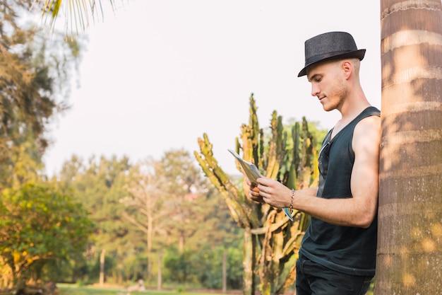 彼は田舎を歩いているときに道順を地図を見て帽子をかぶったハンサムな若い男