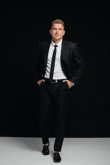 세련된 검은 양복을 입은 잘생긴 청년이 검정색 배경에 포즈를 취하고 있습니다. 스타일리시한 비즈니스맨. 큰 사업가입니다.