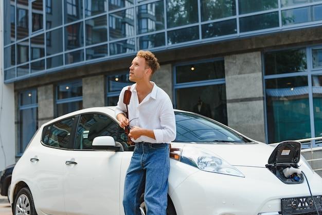 잘 생긴 젊은 남자가 그의 현대적인 전기 자동차를 충전하고 있습니다.