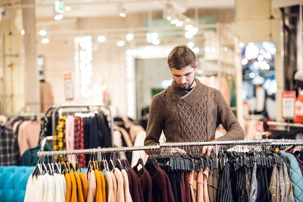 Красивый молодой человек, покупки в магазине одежды