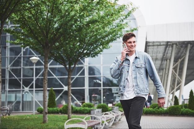 オフィススペースの近くに電話で話しているハンサムな若い男。