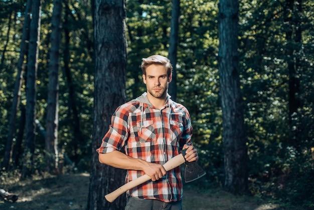Красивый молодой человек с бородой несет под деревом стильный молодой человек, позирующий дровосеком ...