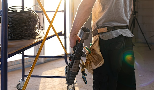 Разнорабочий держит в руке сверлильный инструмент в солнечной комнате.