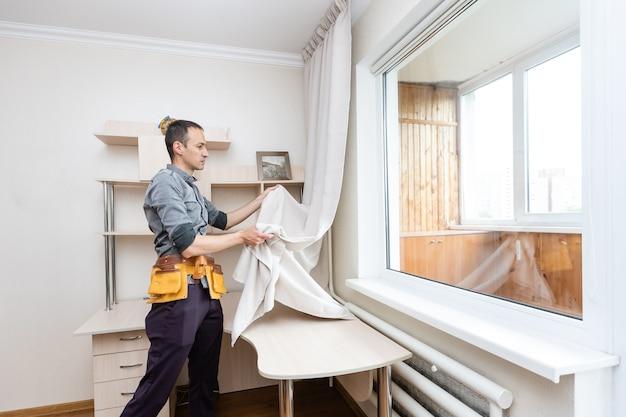 Разнорабочий устанавливает новый карниз для штор, ремонт дома и ремонтные работы.