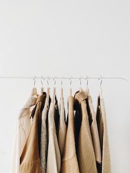 Вешалка теплых красивых женственных бежевых свитеров или пуловеров