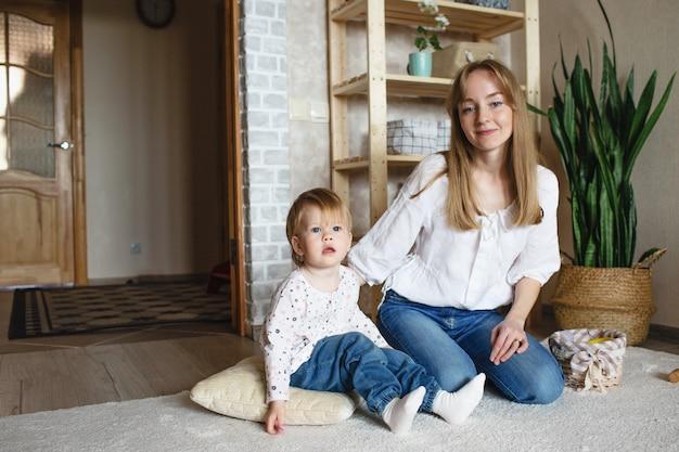 Счастливая и заботливая молодая мама играет со своей маленькой дочкой. с удовольствием проводите время с ребенком. концепция семейного счастья и благополучия