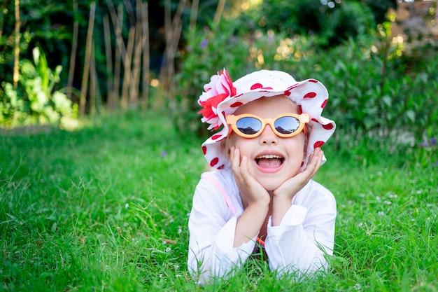 행복하고 즐거운 어린 소녀는 선글라스를 끼고 잔디밭의 푸른 잔디에 누워 있고 여름에는 파나마 모자를 쓰고 웃는다