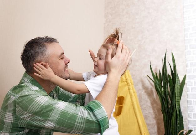 Счастливый и любящий отец играет дома со своей маленькой дочкой