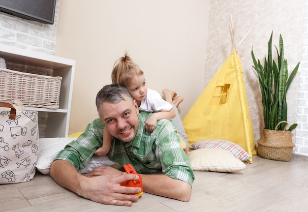 幸せで愛情のある父親は彼の小さな娘と一緒に家で遊ぶ