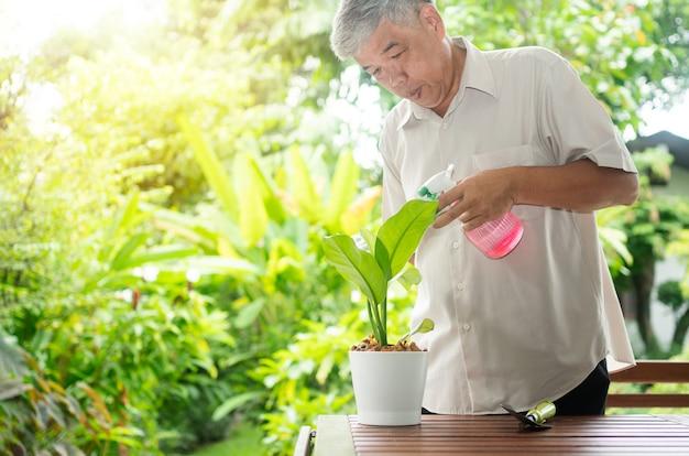 행복하고 웃는 아시아 노인이 은퇴 후 집에서 취미로 나무를 심고 있습니다. 노인을 위한 행복한 생활 방식과 건강의 개념.