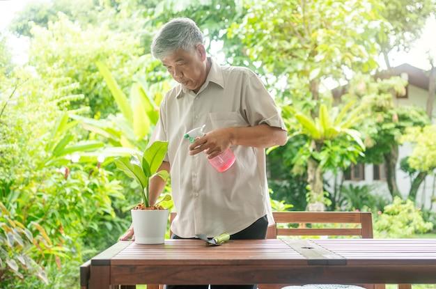 幸せで笑顔のアジアの老人は、家で引退した後、趣味のために植えています。高齢者の幸せなライフスタイルと健康の概念。
