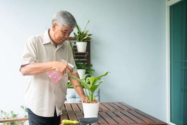 행복하고 웃는 아시아 노인이 집에서 은퇴한 후 취미로 나무를 심고 있다