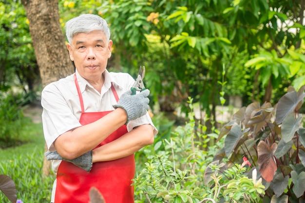 행복하고 웃는 아시아 노인이 집에서 은퇴 한 후 취미로 나뭇 가지와 꽃을 가지 치기하고 있습니다. 노인을위한 행복한 라이프 스타일과 건강의 개념.