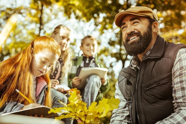 Счастливый и улыбающийся учитель дает урок ученикам в лесу в солнечный день