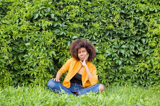 Счастливая и молодая афроамериканка сидит на ступеньках снаружи