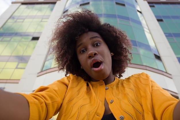 행복하고 젊은 아프리카 계 미국인 여자는 셀카, 클로즈업 걸립니다