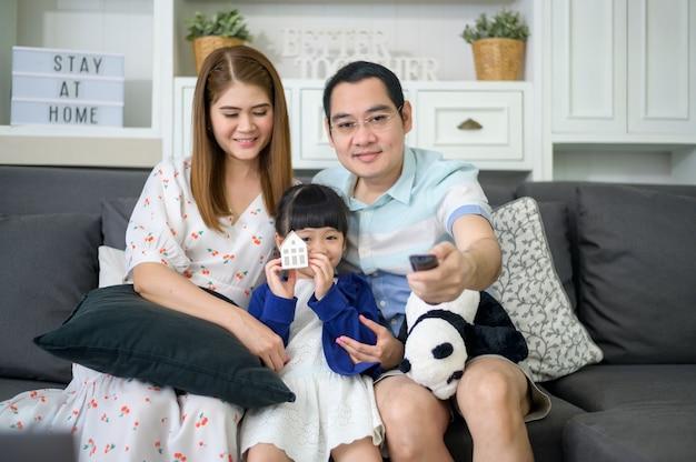 テレビを見て幸せなアジアの家族が週末に家で一緒に時間を過ごしています