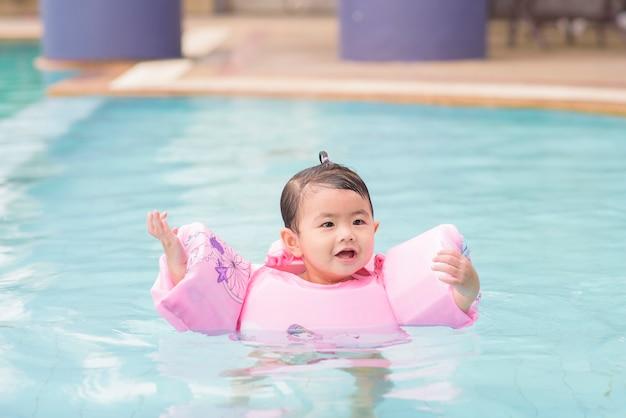 幸せなアジアの母と娘はプール、ライフスタイル、親子関係、家族の概念で水泳を楽しむ