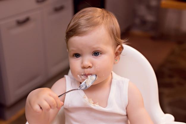 10〜12か月のハッピーベビーは、スプーンで牛乳のお粥を食べます。キッチンのハイチェアで幸せな少女の肖像画