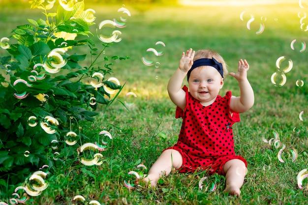 여름에 빨간 바디수트를 입은 행복한 아기가 손으로 비누방울을 잡고 지는 태양, 문자를 위한 공간에서 기뻐합니다
