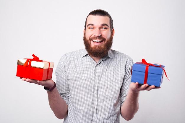 행복한 수염 난 남자가 카메라를보고 어떤 선물을 선택해야할지 두 개의 멋진 선물을 들고 있습니다.