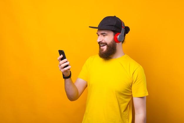 幸せなあごひげを生やした男が彼の電話に話していると同時に音楽を聴いています