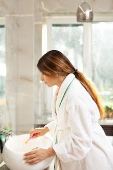 Счастливая красивая беременная женщина в халате чистит зубы. стиль жизни. красивый интерьер. утренний и вечерний распорядок. здравоохранение. стоматологическая уход. фото высокого качества