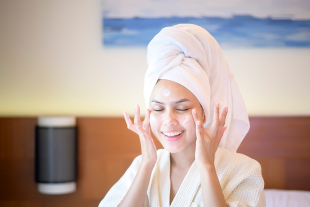 Счастливая красивая женщина в белом халате, наносящая увлажняющий крем на лицо в спальне, концепция ухода и лечения кожи