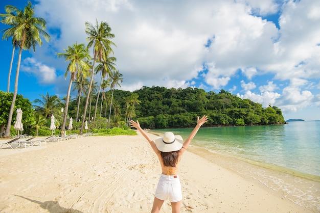 노란색 비키니 입은 행복한 아름다운 여자가 해변에서 즐기고 휴식