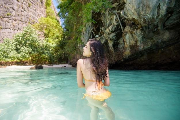 黄色い水着を楽しんで、澄んだ海、夏、休日のコンセプトでリラックスした幸せな美しい女性