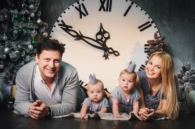 큰 시계의 배경에 대해 집의 새해 인테리어에 쌍둥이 자녀와 함께 행복한 대가족.