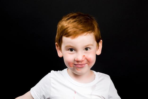 행복한 소년은 익은 딸기, 딸기 디저트를 먹는 동안 여섯 살짜리 아이의 근접 촬영 초상화를 먹는다