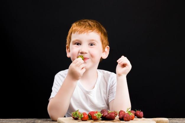幸せな男の子は熟したイチゴを食べる