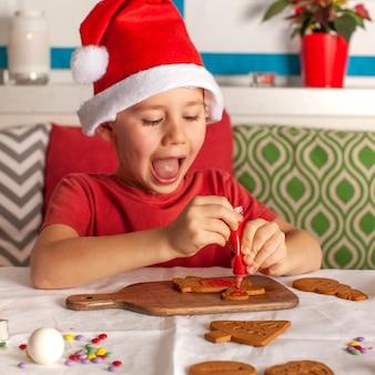 サンタクロースの帽子をかぶった幸せな少年がキッチンのクリスマスライトで生姜のクッキーを飾ります
