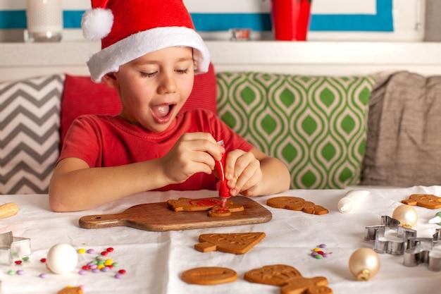 サンタクロースの帽子をかぶった幸せな少年がキッチンで生姜のクッキーを飾ります